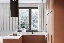 a very chic minimalist matte terra cotta kitchen with white stone countertops and a black hood and fixtures is wow