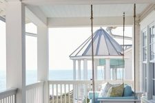a very simple beach porch with a white hanging daybed with blue upholstery and a blue side table plus a view