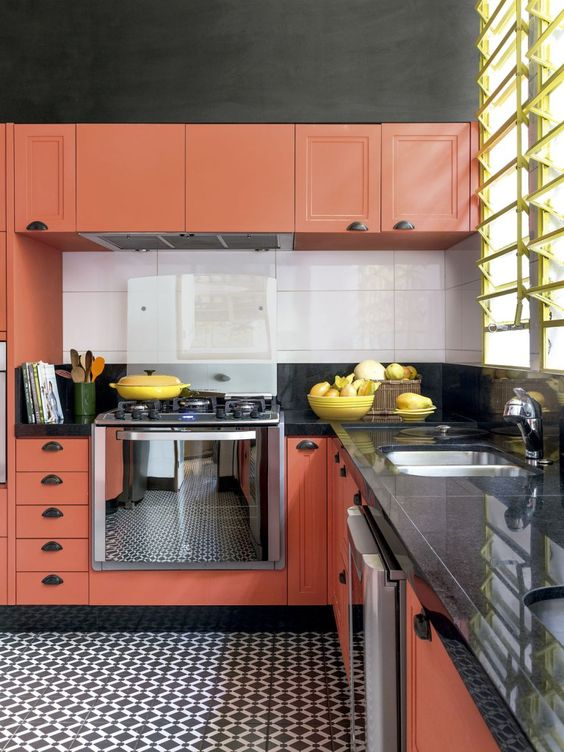 a vibrant kitchen with burnt orange cabinets, a mosaic tile floor, black countertops and a white tile backsplash