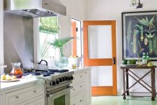 a vibrant tropical kitchen with a green floor, an orange door, white cabinets, a bright tropical wall art