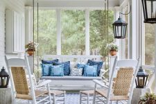 a vintage coastal porch with white furniture, blue pillows, a blue printed rug, potted greenery and candle lanterns