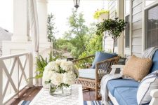 a vintage coastal porch with white wooden and rattan furniture, blue and white textiles, a white table and a striped rug