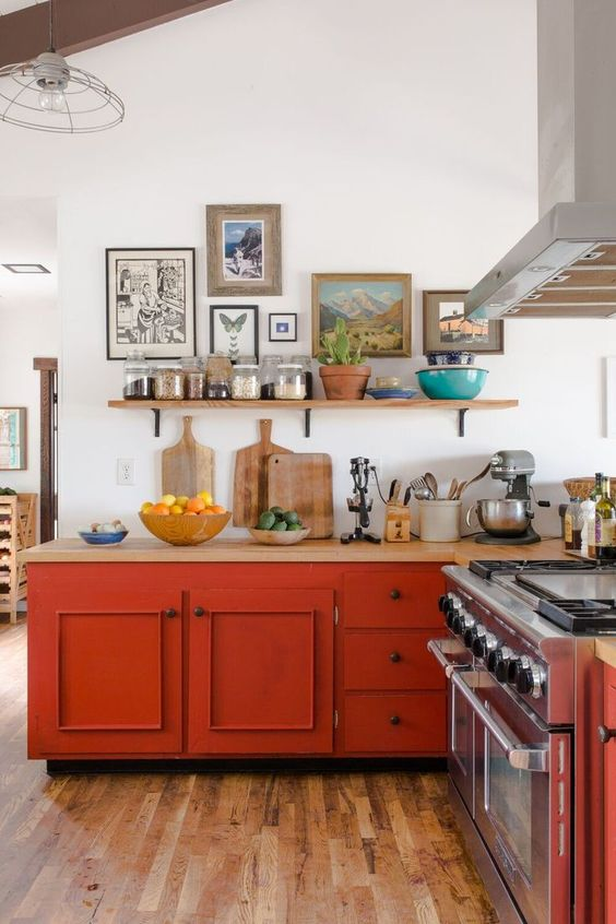 a vintage farmhouse kitchen in neutrals but with burnt orange cabinets, light stained countertops and a pretty gallery wall