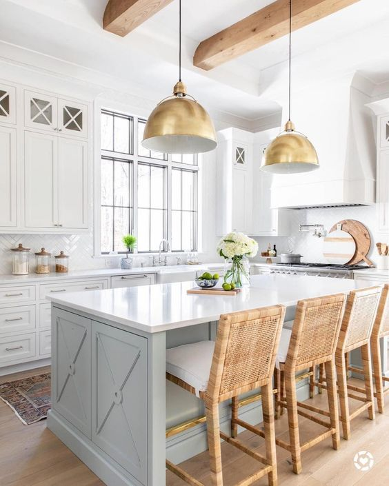 a vintage infused coastal kitchen with white cabinetry, a light blue ktichen island, rattan stools and gold pendant lamps
