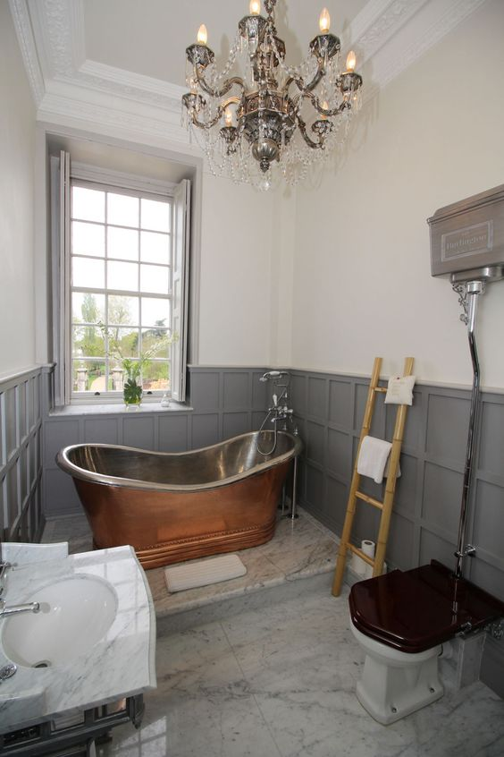 a vintage-inspired bathroom with grey paneling, a crystal chandelier, a copper rub and a white marble sink is wow