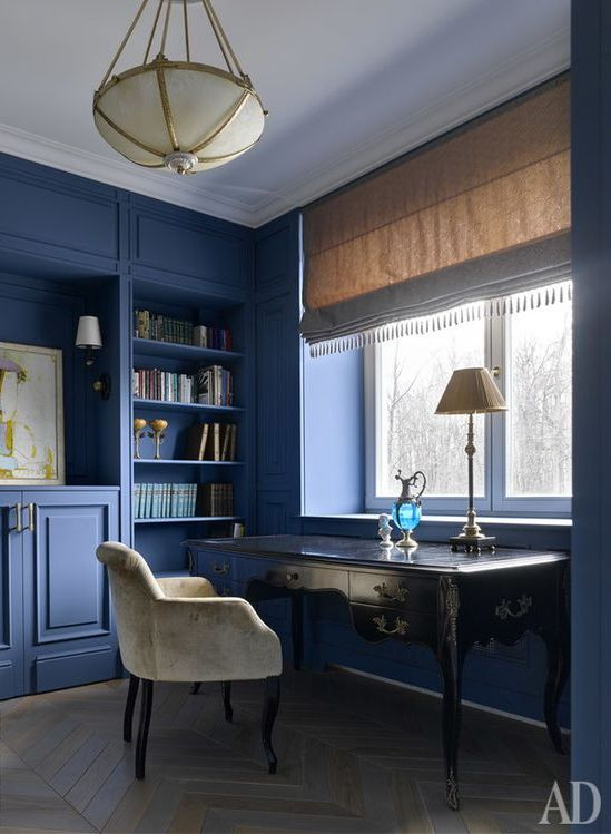 a vintage-inspired blue home office with built-ins and paneling, with a refined black desk and velvet chair and chic lamps