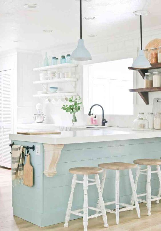 a vintage inspired coastal kitchen with white cabinets, a light blue kitchen island and matching lamps over it, open shelving and vintage stools