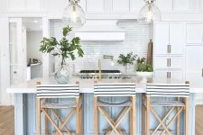 a vintage-inspired coastal kitchen with white cabinets, a light blue kitchen island, striped stools and glas spendant lamps