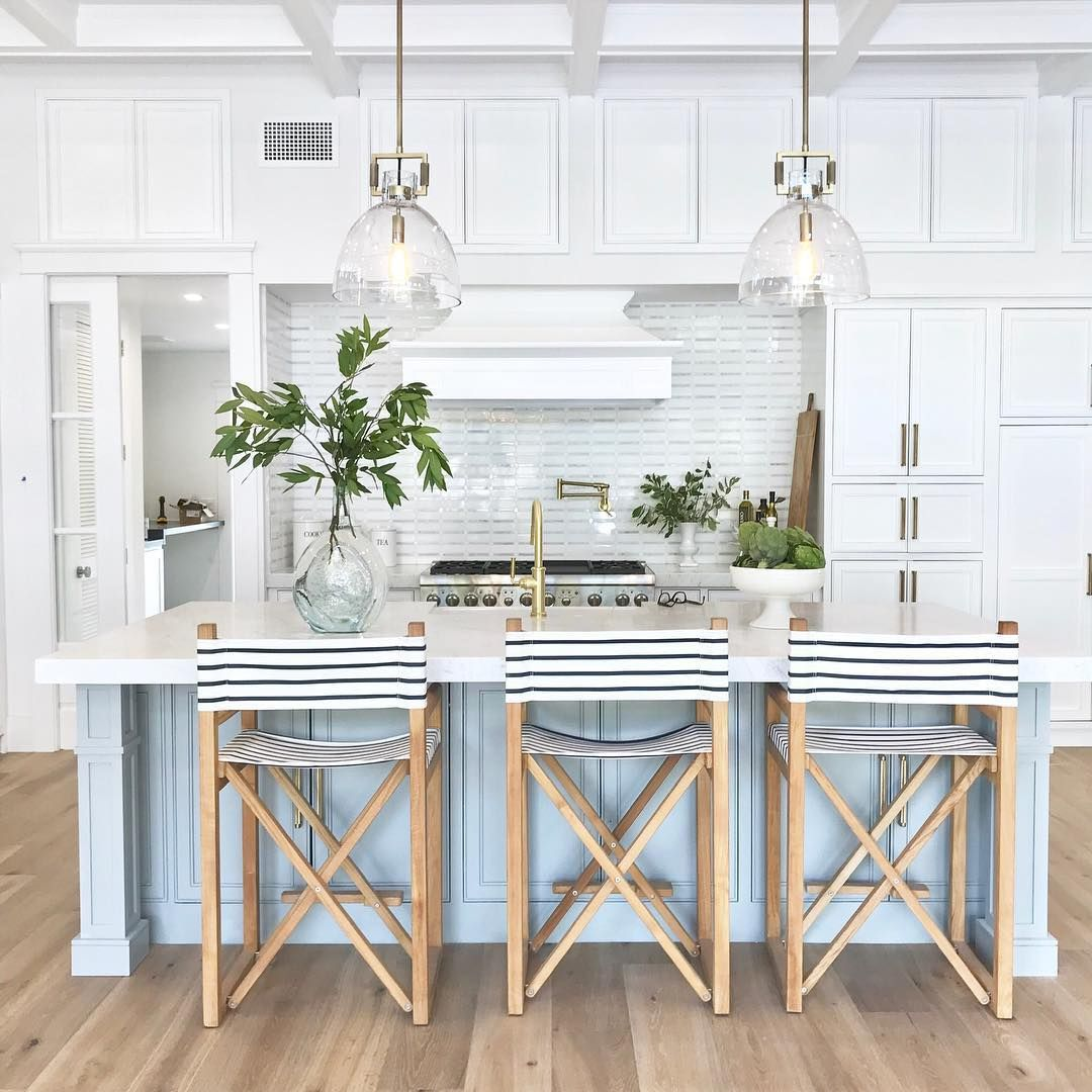 a vintage inspired coastal kitchen with white cabinets, a light blue kitchen island, striped stools and glas spendant lamps