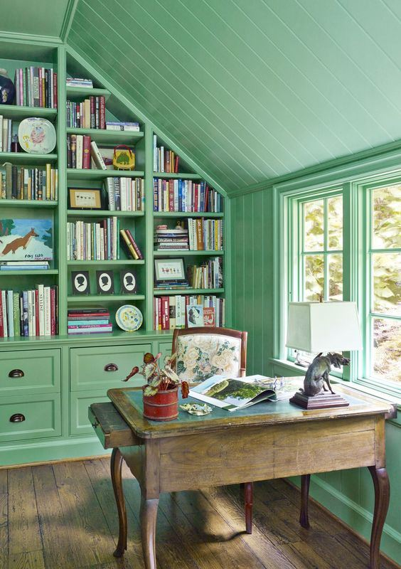 a vintage-inspired home office in sage green, with a rough wooden desk, a large wall storage unit taking the whole wall