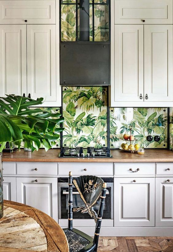 a vintage-inspired neutral tropical kitchen with large cabinets, tropical leaf wallpaper, touches of black for drama