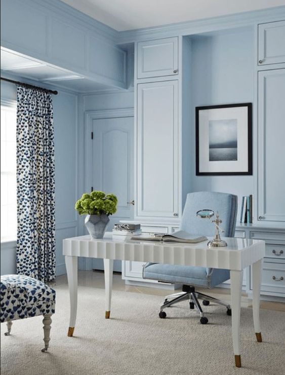a vintage inspired powder blue home office with built in storage units, a white desk and printed textiles that catch an eye