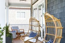 a welcoming beach porch with a blue chair and an ottoman and hanging rattan chairs with blue pillows