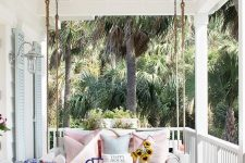 a welcoming beach porch with a hanging sofa, a comfy lounger, pastel textiles, a wood table and blooms