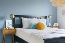 a welcoming bedroom with a blue accent wall, a navy bed, mid-century modern stained nightstands and a woven lamp
