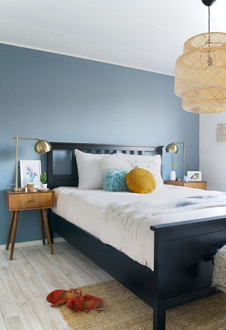 a welcoming bedroom with a blue accent wall, a navy bed, mid century modern stained nightstands and a woven lamp