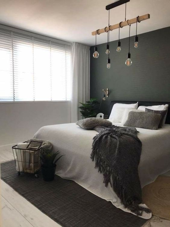 a welcoming bedroom with a graphite grey accent wall, white and dark grey bedding, a dark grey rug and a cool pendant lamp