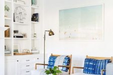 a welcoming coastal living room with blue furniture, indigo pillows, a wooden table, a leather ottoman and a beach artwork