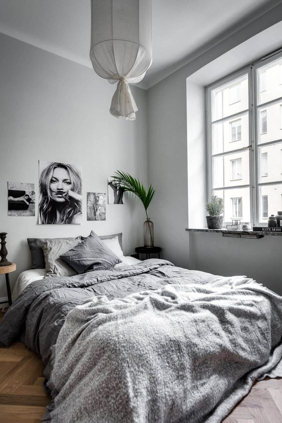 a welcoming dove grey bedroom with grey walls, a black and white gallery wall, grey bedding and a lamp plus greenery
