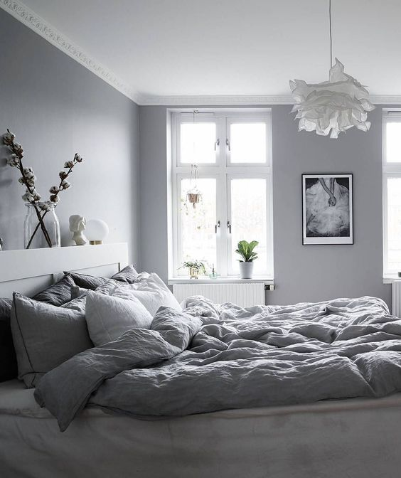 a welcoming grey Nordic bedroom with dove grey walls, grey bedding, a fluffy pendant lamp and catchy artworks