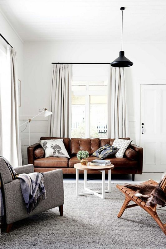 a welcoming neutral living room with a brown leather sofa, a leather stool and a grey chair is cool and stylish