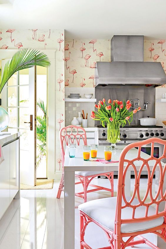 a whimsy tropical kitchen with flamingo wallpaper, white cabinets and a table, pink rattan chairs and blooms and greenery