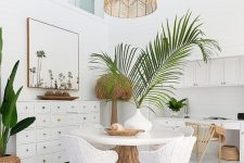 a white tropical home office with white furniture, woven and wooden chairs, a woven pendant lamp and potted plants