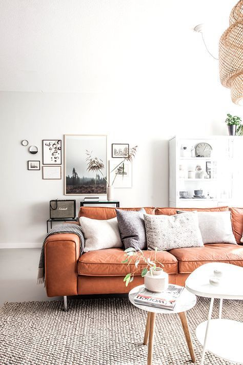 an airy and chic living room done in neutrals with a bright amber leather sofa is very cool and welcoming