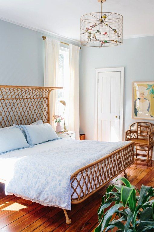 an airy blue bedroom with light blue walls, a rattan bed and chairs, light blue bedding and a bold artwork