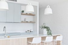 an airy coastal kitchen with light blue cabinetry, a large wooden kitchen island, white pendant lamps, white wicker stools