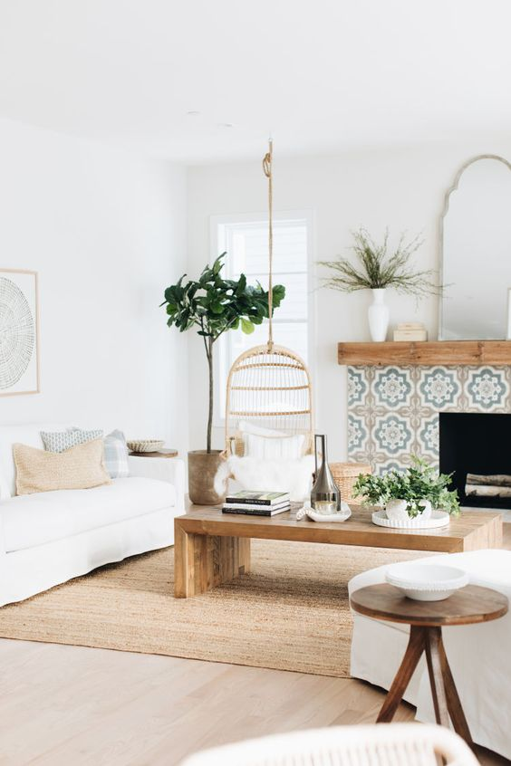an airy coastal living room with white furniture, a tiled fireplace, potted greenery, a rattan suspended chair and a mirror