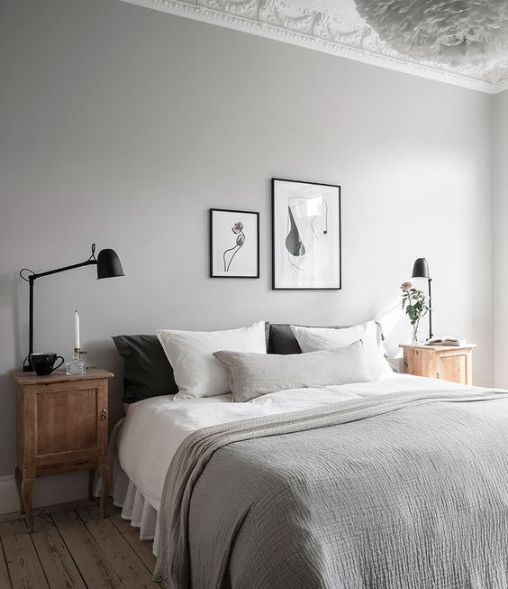 an airy dove grey bedroom with wooden nightstands, black lamps, a black and white gallery wall and grey bedding