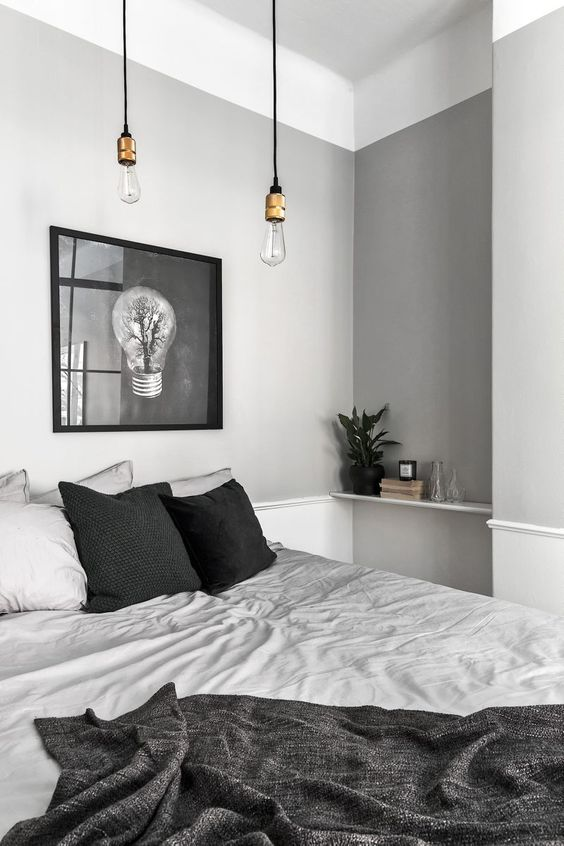 an airy grey Scandinavian bedroom with dove grey walls, grey and black bedding and a dark artwork plus pendant lamps