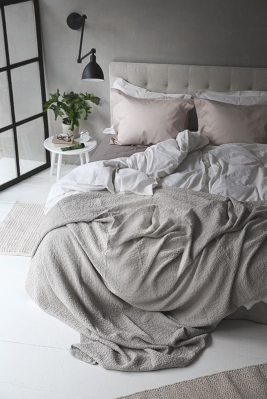 an airy grey bedroom with an upholstered dove grey bed, grey and blush bedding, a potted plant and touches of black