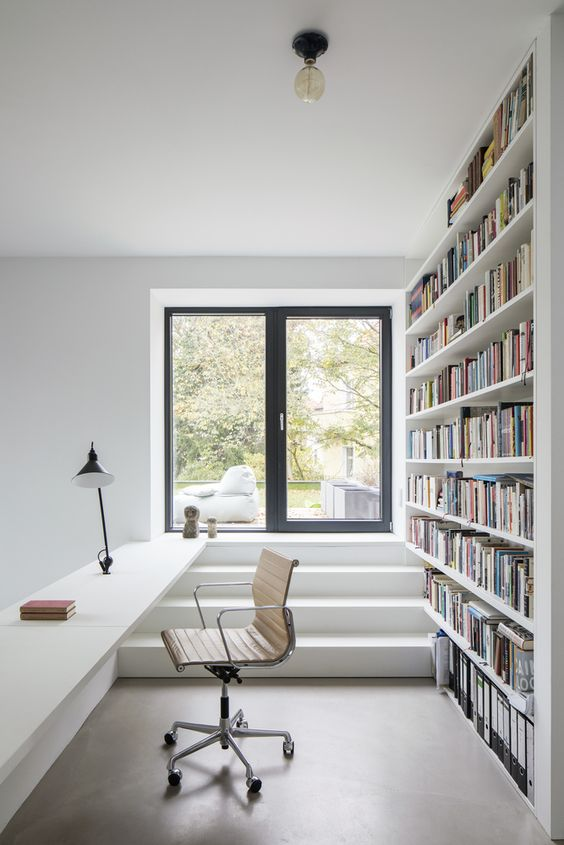an airy white home office and library with an oversized bookshelf that divides spaces and a built-in desk