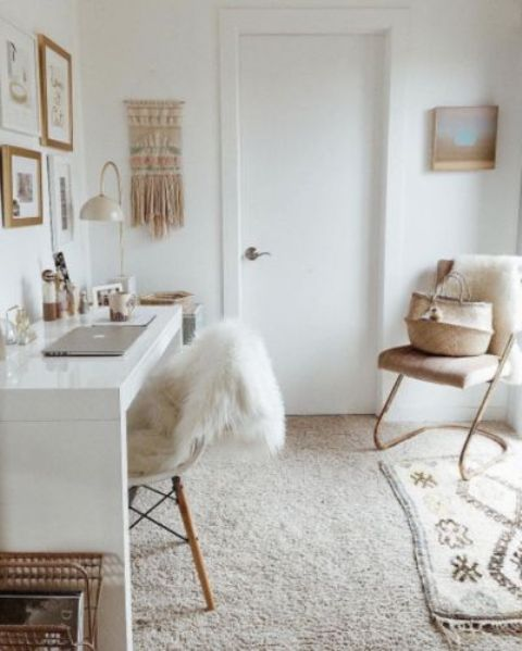 an all-neutral home office with neutral textiles, a gallery wall, a macrame hanging and a comfy chair