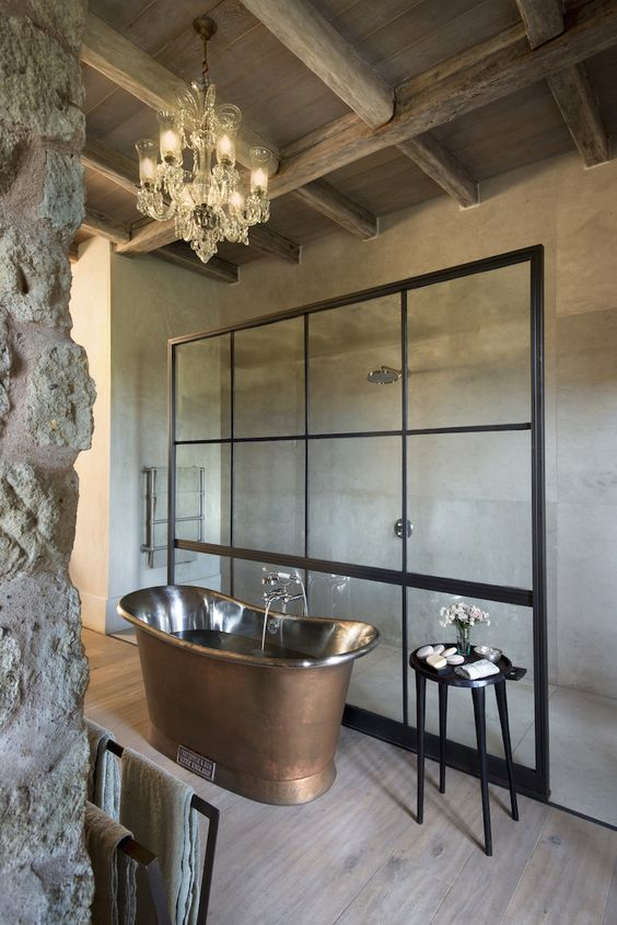 an eclectic bathroom with a luxurious copper tub, a vintage chandelier and a black stool plus wooden beams on the ceiling