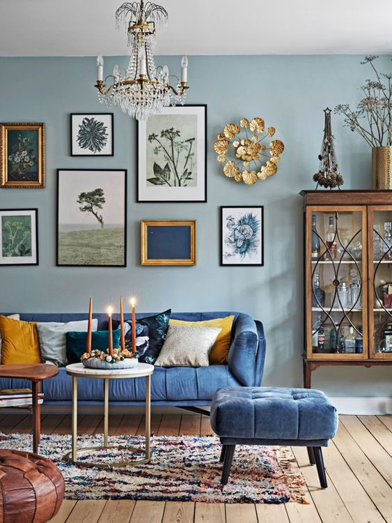 an eclectic living room with light blue walls, a bold blue sofa and a matching ottoman, a gallery wall and a crystal chandelier