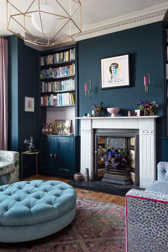 an eclectic living room with navy walls, a light blue ottoman, gold touches and a leopard print sofa