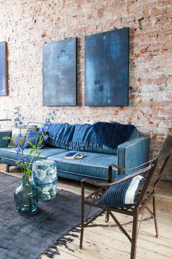 an eclectic living space with an exposed brick wall, a classic blue sofa, indigo artworks and pillows and a black rug