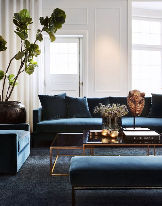 an elegant and laconic living room with white walls, blue furniture, glass tables and touches of gold for more chic
