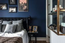 an elegant attic bedroom with a navy accent wall, a black bed, a gallery wall, a glass storage unit is chic