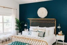 an elegant bedroom with a teal wall, a woven bed, a turquoise bench, a gold chandelier and a boho rug