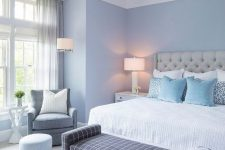 an elegant bedroom with light blue walls, a grey leather bed, a windowpane print bench, a vintage chandelier and greys here and there