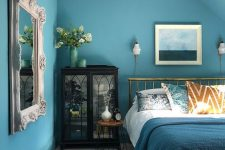 an elegant blue bedroom with a gold bed, a dark glass buffet, a vintage mirror and a chic seaside-themed artwork