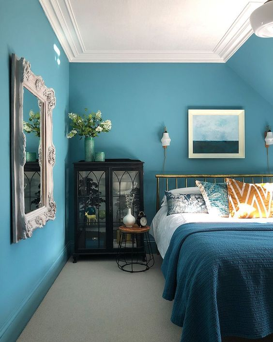 an elegant blue bedroom with a gold bed, a dark glass buffet, a vintage mirror and a chic seaside themed artwork