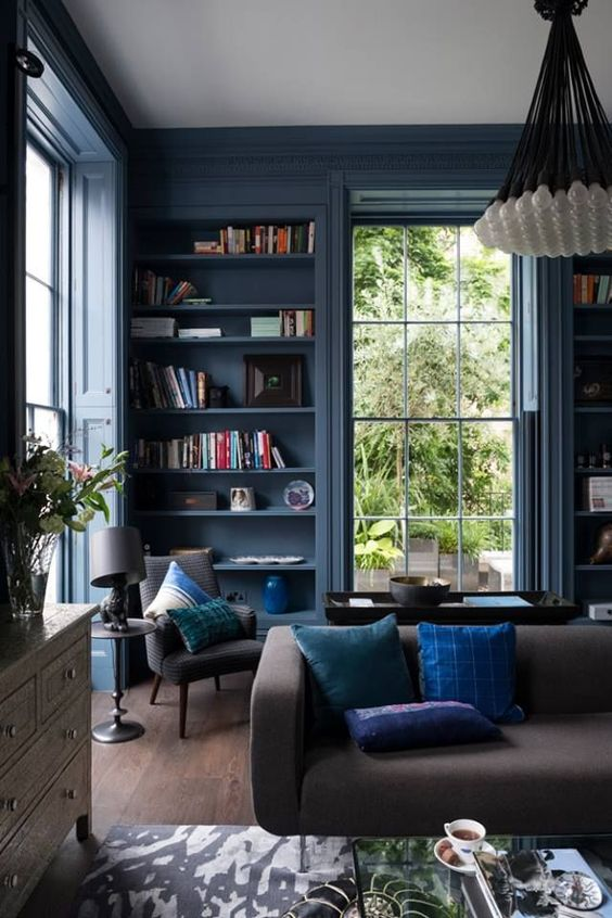 an elegant blue living room with blue walls and built in shelves, grey and brown furniture, potted plants and a cluster chandelier