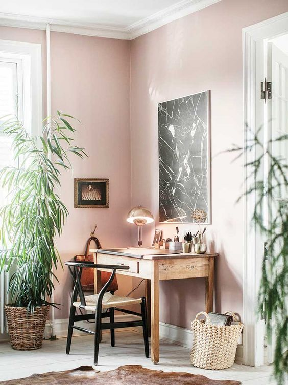 an elegant home office with light pink walls, a vintage desk and chair, a black marble artwork and a statement plant