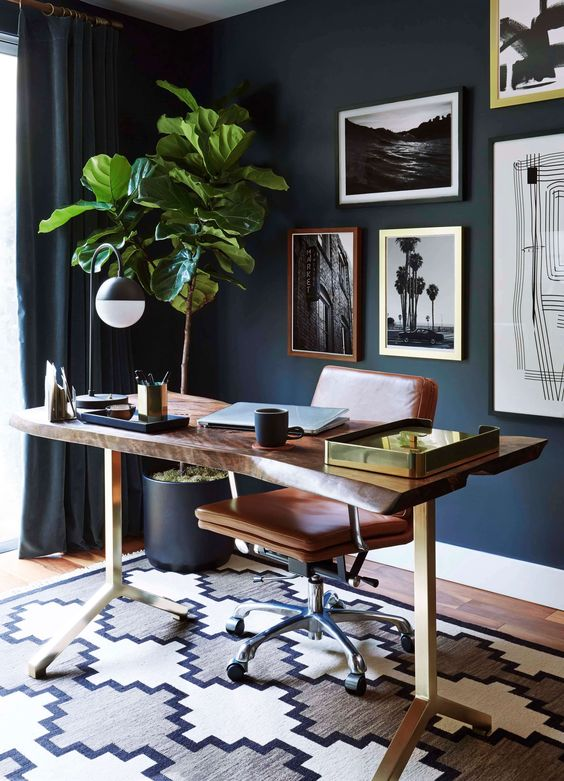 an elegant navy home office with a wood slab desk, a leather chair, a chic gallery wall and a statement potted plant