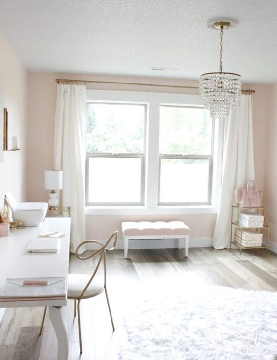 an elegant pastel feminine home office with blush walls, white and blush furniture, a crystal chandelier and gold touches